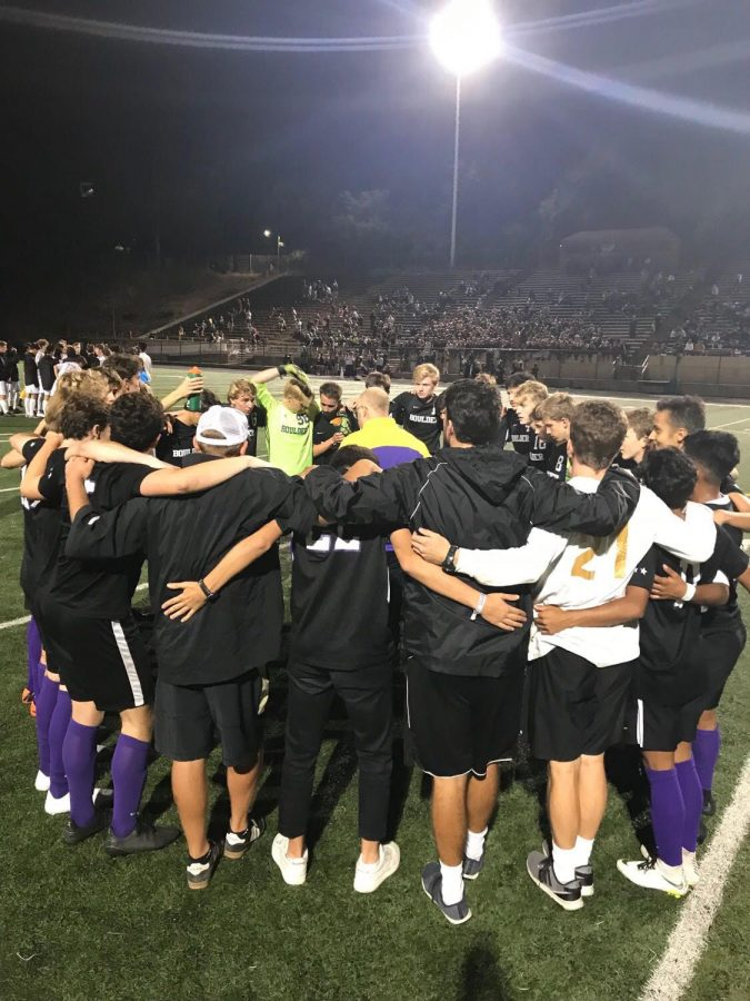 The varsity boys soccer team huddles up during a game. Photo via Boulder High Yearbook.