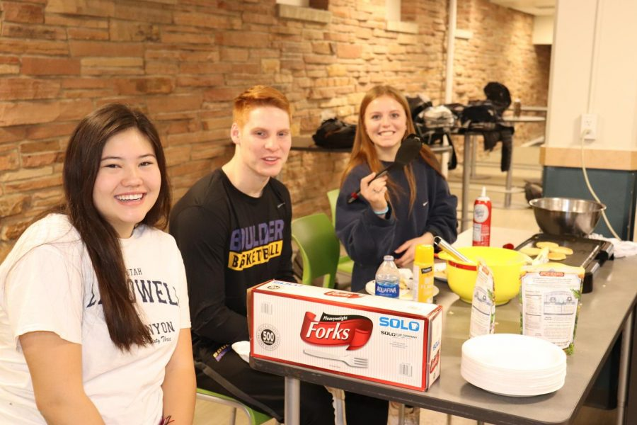 Picture #3: Student Council members Maya Roberts, junior, Drake Arthur, junior, and Maddie Hawk, senior, cooking the pancakes. Photo via Lara Spijkerman.