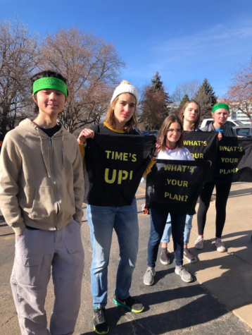 Student members of the Sunrise Movement Club at Boulder hold up protest signs outside the Denver Capitol building on January 9th.
