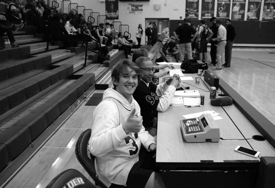 Alex Rucker, junior, helping out at the scorer's table. Rucker supports his team in spite of the injury. Photo by Elijah Boykoff.