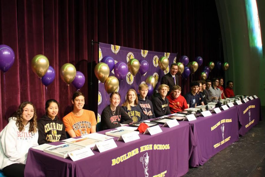 The proud student athletes pose for a photo on the stage in the auditorium after signing.