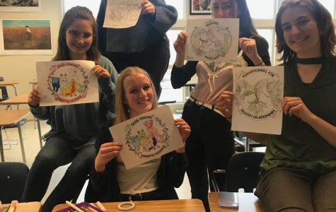 Amaya Brooks, junior, Lili Stevens, Rory Mendelow Sara Proctor and Ellory Boyd, seniors, posed with pictures they colored during the first Student Alliance for Consent and Sexual Safety meeting.