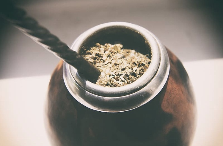 Yerba Mate is traditionally consumed through a filtered metal straw and held in a gourd.
