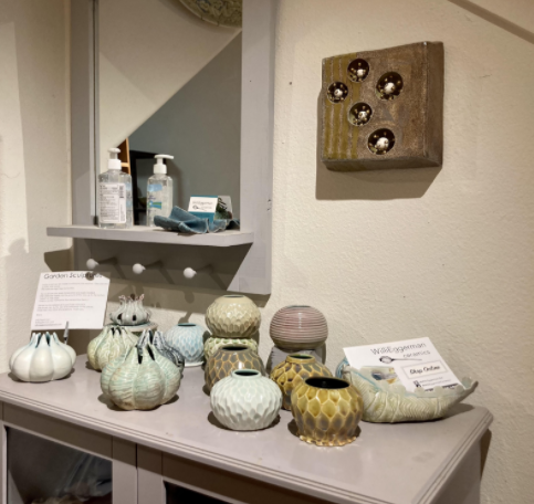A display of pottery along with hand sanitizer in Willi Eggerman's studio.