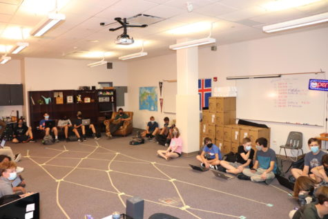 Students sit on the floor, disappointed that they have no furniture. Luckily, Mrs. Zimmerman is a creative and flexible teacher.